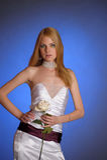 Blonde en un vestido de noche blanco elegante con la rosa del blanco en su mano Foto de archivo libre de regalías