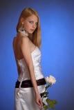 Blonde en un vestido de noche blanco elegante con la rosa del blanco en su mano Imagenes de archivo