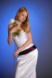 Blonde en un vestido de noche blanco elegante con la rosa del blanco en su mano Imágenes de archivo libres de regalías