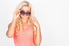 Blonde en un vestido rosado y gafas de sol Fotos de archivo libres de regalías