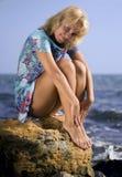 Blonde en una roca Imagen de archivo libre de regalías