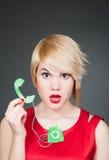 Blonde en vestido rojo con el pequeño modelo del teléfono retro Foto de archivo