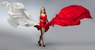 Blonde en vestido rojo y blanco ventoso imágenes de archivo libres de regalías