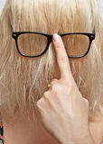 Blonde en vidrios con la cara cerrada del pelo Foto de archivo