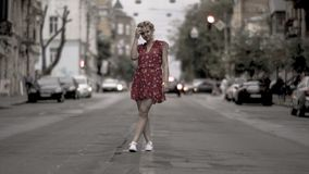 Blonde encantador en el vestido ligero que presenta para la cámara en el camino Foto de archivo
