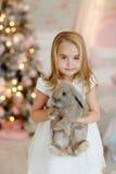Blonde encantador muy bonito de la niña en las risas blancas del vestido y Imagen de archivo