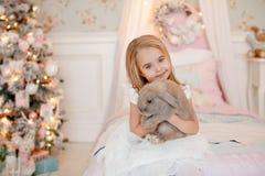 Blonde encantador muy bonito de la niña en las risas blancas del vestido y Fotos de archivo libres de regalías