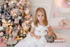 Blonde encantador muy bonito de la niña en las risas blancas del vestido y Fotografía de archivo