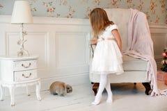 Blonde encantador muy bonito de la niña en una situación blanca del vestido Fotos de archivo libres de regalías