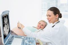 Blonde enceinte gaie ayant un balayage d'ultrason images stock