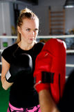 Blonde engaged boxing with trainer Stock Photo
