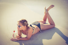 Blonde enjoying a cocktail on the beach Stock Photo