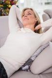 Blonde Entspannung auf der Couch am Weihnachten Stockbilder
