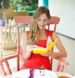 Blonde Entspannung im Kaffee und Lesen des Buches Stockfotos