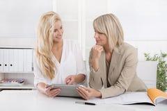 Blonde erfolgreiche attraktive Geschäftsfrau zwei, die in einem Team arbeitet Stockfoto