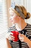 Blonde erwägende schöne junge Frau des Pinupmädchens mit einer roten Schale, die wistfully heraus das Fensterporträt schaut Stockfotografie