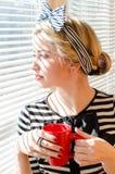 Blonde erwägende schöne junge Frau mit der roten Schale, die wistfully durch Fensterporträt schaut Stockfotos
