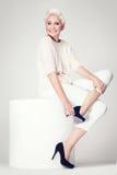 Blonde erwachsene Frau, die im Studio aufwirft Stockfotos