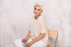 Blonde erwachsene Frau, die im Studio aufwirft Stockfotografie