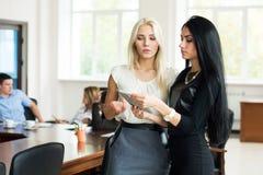 Blonde et brune de deux jeune femmes d'affaires avec un compu de comprimé Photo libre de droits