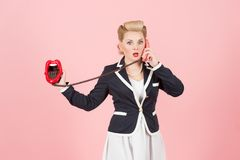 Blonde expressive girl in vintage style calling with cord lips phone. Pin-up make up with red lips and vintage telephone girl. Blonde curls girl in vintage stock photo