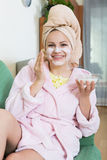 Blonde with face pack relaxing on sofa indoors Stock Images