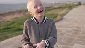 Blonde Fahrten des lustigen Jungen ein Roller entlang der Promenade stock footage