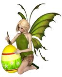Blonde Fairy Painting an Easter Egg Stock Photography