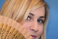 Blonde with Fan. Beautiful blonde with gorgeous eyes holding fan stock photo