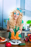 Blonde fashion funny on kitchen with pasta and Stock Photography