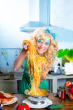Blonde fashion funny on kitchen with pasta and Royalty Free Stock Photo