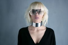 Blonde fashion futuristic silver glasses girl. Gray background stock image