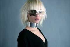 Blonde fashion futuristic silver glasses girl. Gray background Royalty Free Stock Photos