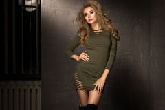 Blonde fashion girl with long and shiny curly hair . Beautiful model in khaki dress with wavy hairstyle Stock Photography