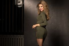 Blonde fashion girl with long and shiny curly hair . Beautiful model in khaki dress with wavy hairstyle Stock Image