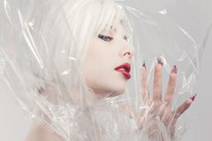 Blonde fashion model in plastic Stock Images