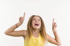 Blonde feliz con el pelo rizado, muchacha adolescente que destaca su dedo índice Foto de archivo