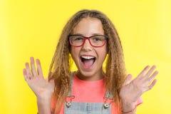 Blonde feliz con el pelo rizado que gesticula, fondo amarillo brillante del adolescente del estudio Imagenes de archivo