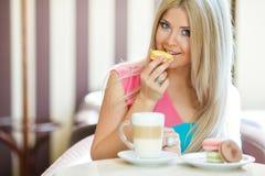 Blonde feliz en una tabla en un café Imagen de archivo libre de regalías