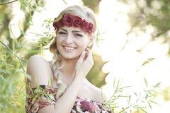 Blonde feliz que lleva una corona de la flor Fotografía de archivo