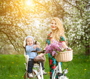 Blonde female with city bicycle with baby in bicycle chair stock photography
