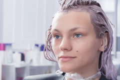 A blonde female client coloring hair in hairdressing salon Stock Image