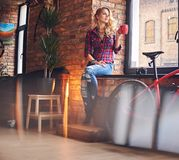 Blond female drinks hot coffee near the window. Blonde female dressed in a jeans and fleece shirt, drinks hot coffee near the window in a room with loft Royalty Free Stock Photo