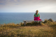 A Blonde Female Hiker Rests on a Bench on the Cliffs. Royalty Free Stock Images