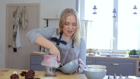 blonde female making cream for decorating cupcakes doing hobby woman puts the cream in - Woman Decorating Cupcakes