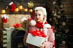 Blonde female model dressed in a Santa Claus hat. Cute young woman with santa hat. Euphoria. Fashion portrait of girl. Indoors with Christmas tree stock photos