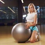 Blonde female model kneeling and holding balance ball Royalty Free Stock Photos