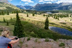 Blonde female photographer using smart phone to take tourist pic. Tures at Molas Pass in the Million Dollar Highway in the San Juan mountains of Colorado stock photos