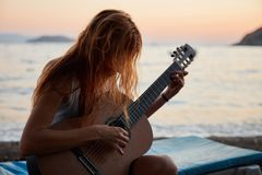 Blonde female playing acoustic guitar on the beach Royalty Free Stock Photos