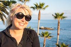 Blonde female portrait in Laguna Beach California coastline, wearing sunglasses and smiling. Blonde California girl portrait with palm trees in background in stock photo